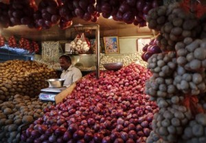 A vendor waits for customers at his vegetable stall at a wholesale fruit and vegetable market in Mumbai